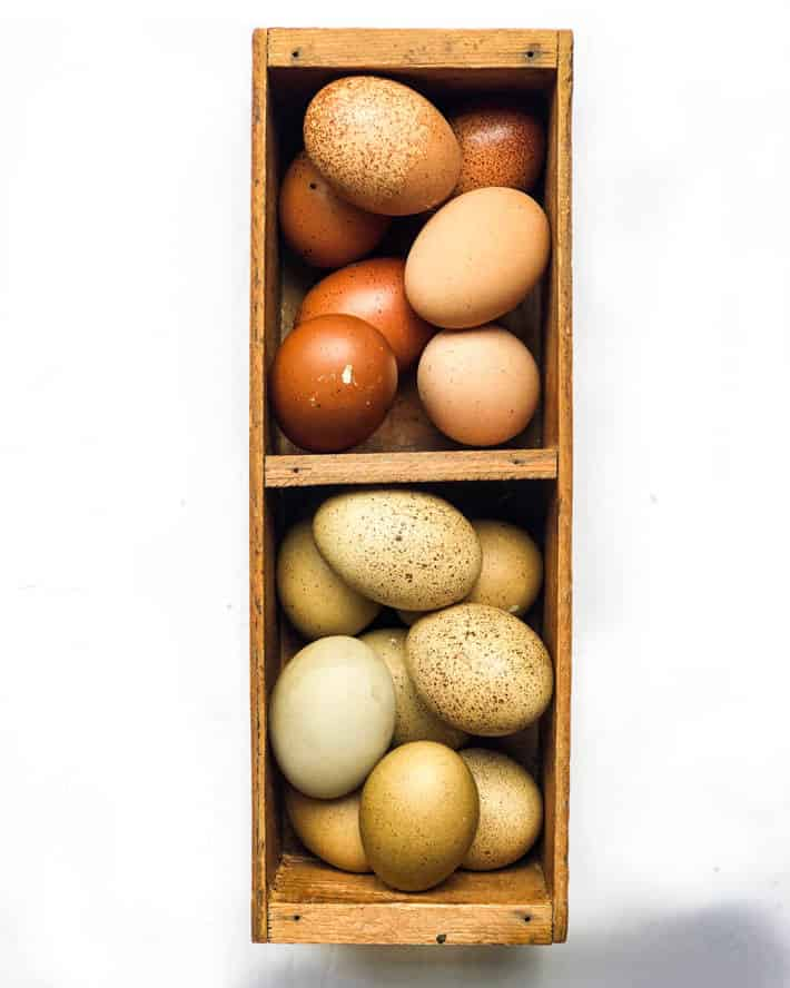 Eggs in various shades of brown and pale-olive in a wooden crate on a white background.