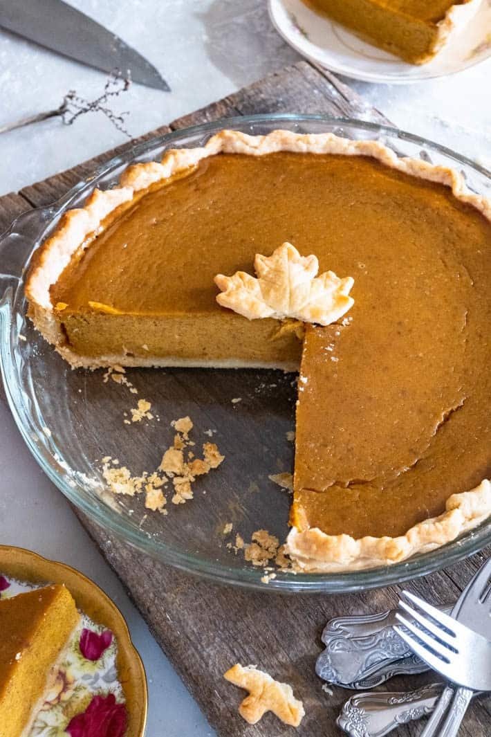 A delicious looking pumpkin pie in a glass pyrex dish with one piece out of it, crumbs around and a