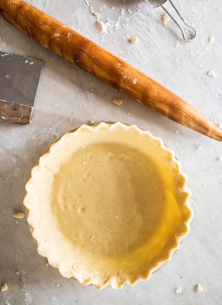 Uncooked pie shell on a flour covered marble countertop with french rolling pin to the side.