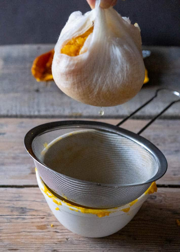 Lifted cheesecloth full of pumpkin puree, draining into bowl.