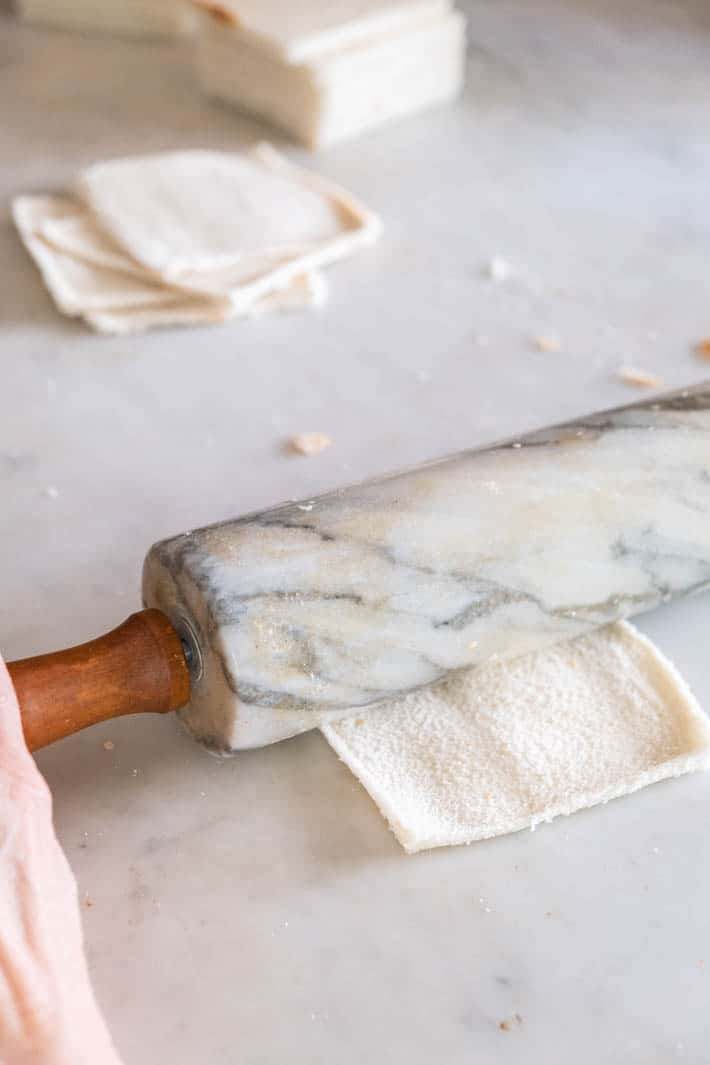 Marble rolling pin being used to flatten white bread, on a marble countertop.