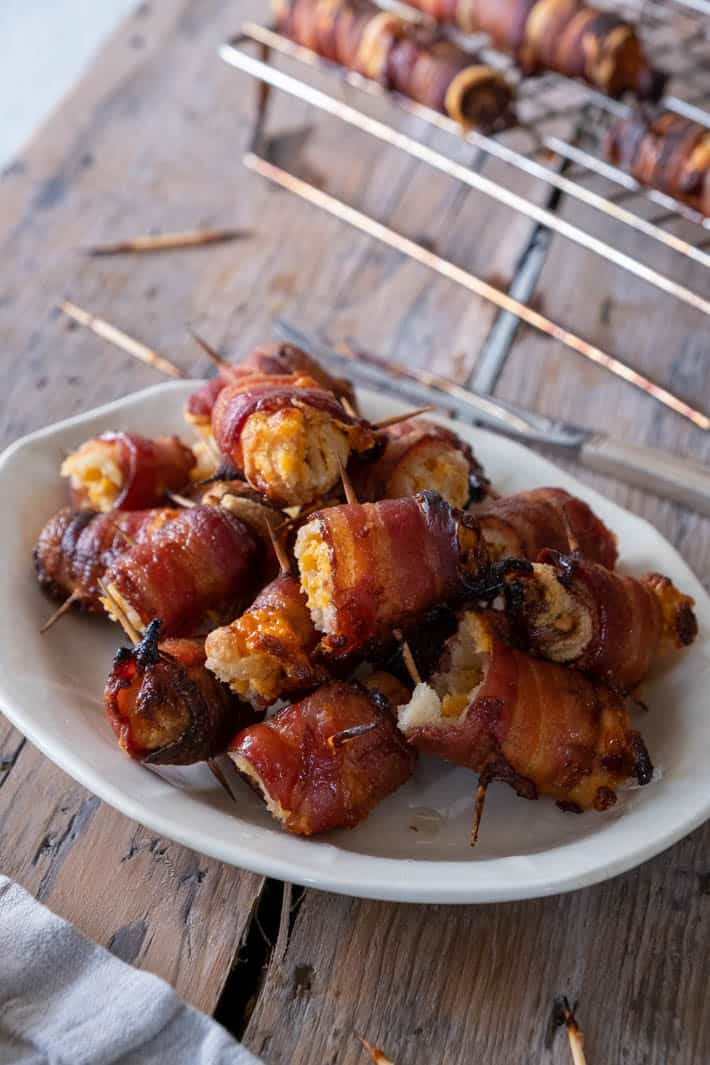Crispy bacon wraps mounded on an ironstone plate set on barnboard.