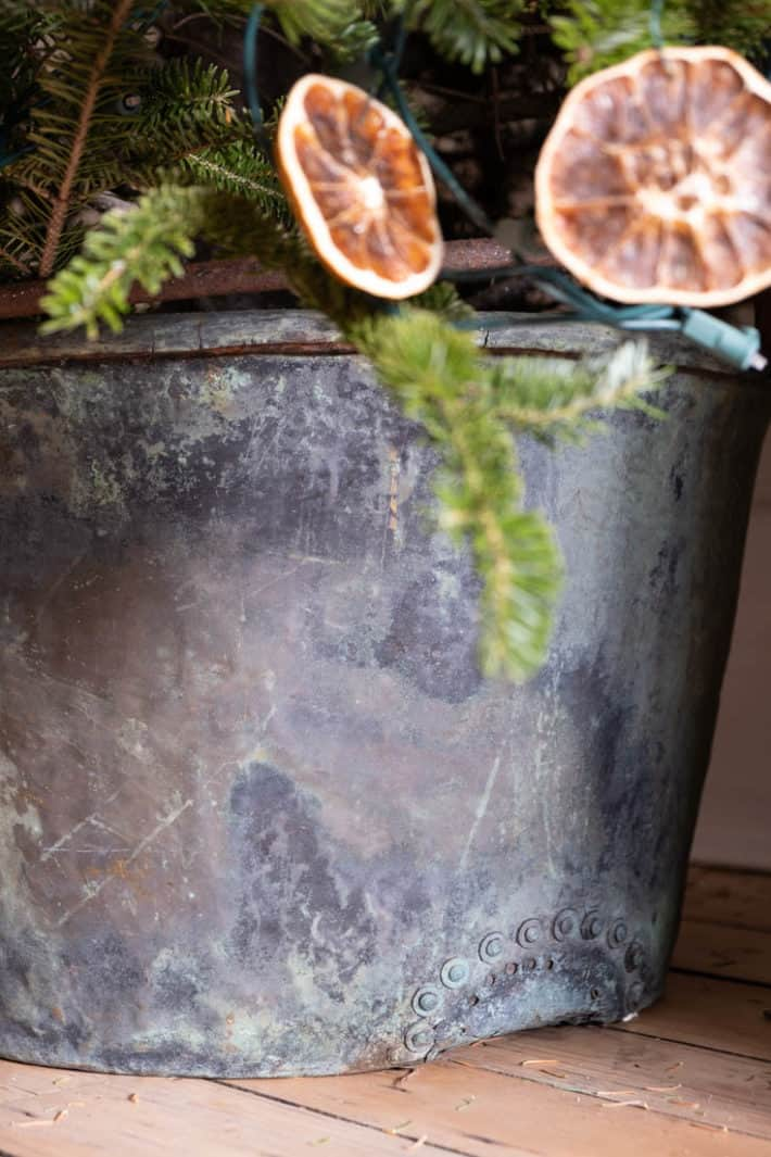 Very large antique copper pot with rivet repair on the bottom.
