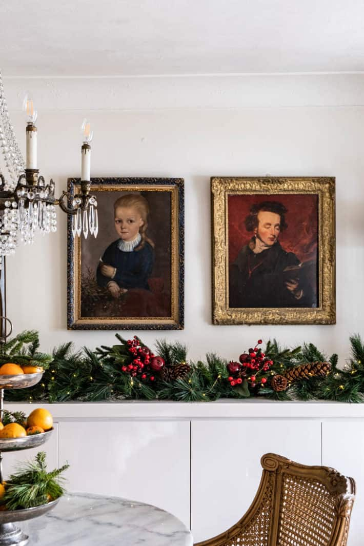 Two vintage oil portraits in gold frames, side by side over modern white lacquer buffet with lush Christmas garland with red berries.