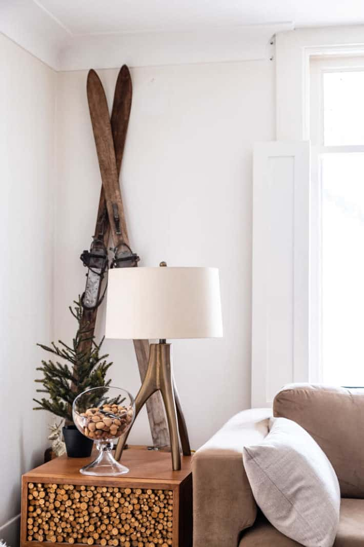 Vintage wood skiis propped against a white wall with an organic brass lamp in front and a modern glass bowl of nuts.