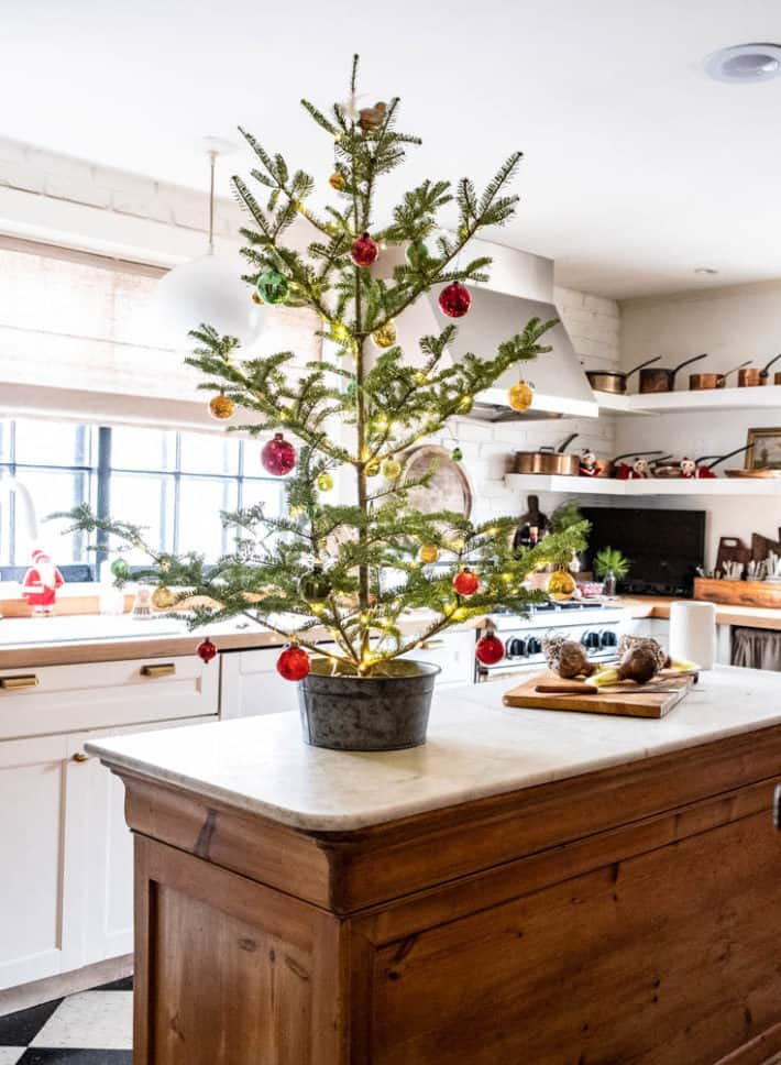 Christmas tree on kitchen island with copper pots on shelves in the background.