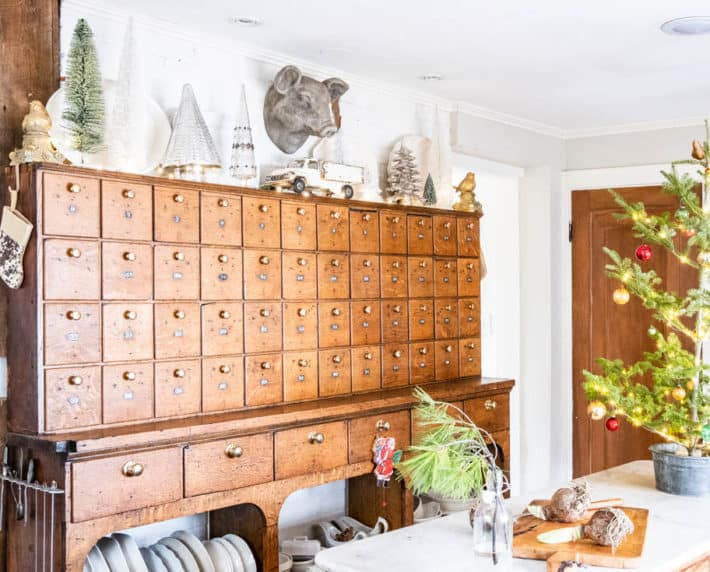Antique hardware cabinet with Christmas trees on top and ironstone on shelving below.