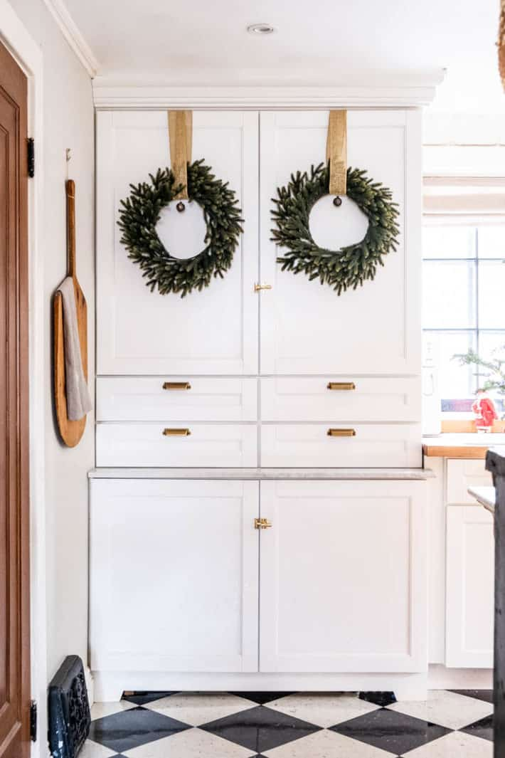 White Martha Stewart pantry cabinets with simple wreaths hung from burlap ribbon on the doors.