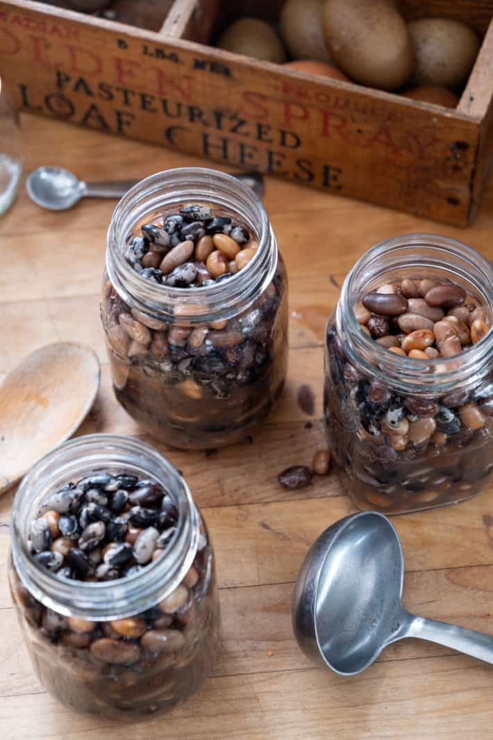 A butcher block countertop with 3 mason jars filled with an array of interesting beans ready to be canned.