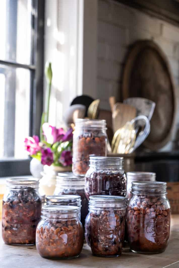 Stacked jars of home canned beans in front of a sunny window with flowers in behind.