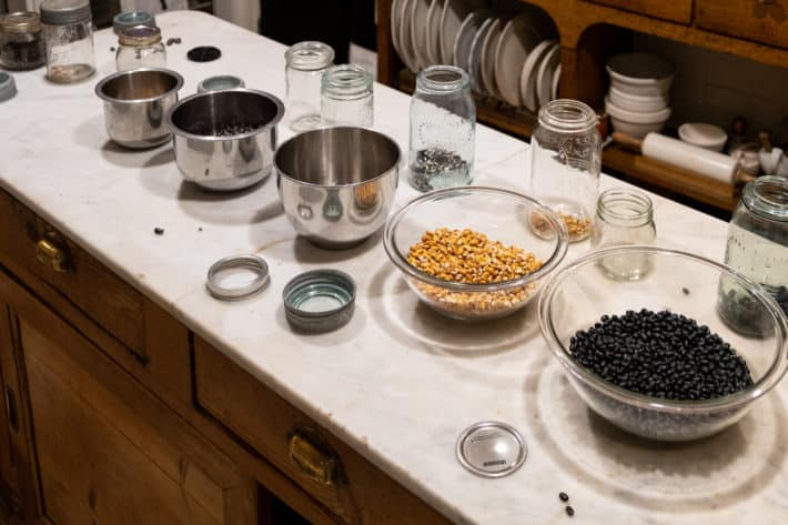 Heirloom dried beans in bowls running across an old white marble candy counter.