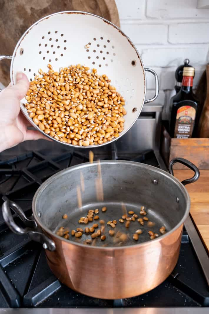 Dumping a colander of presoaked Zuni Gold beans into a large copper pot for boiling.
