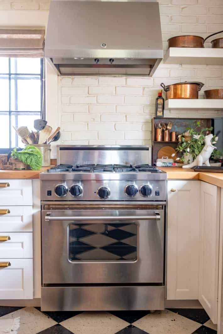 Stainless steel Blue Star Range with a stainless hood above sits in front of a white brick wall with copper pots on floating shelves.