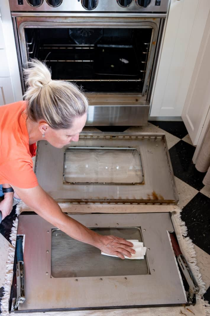 Hand cleaning between the glass of an oven door with microfiber.