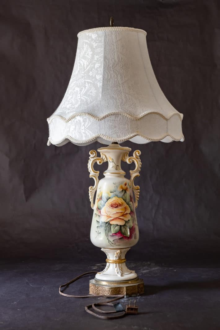 Vintage ceramic lamp with shade and hand painted roses on a black background.