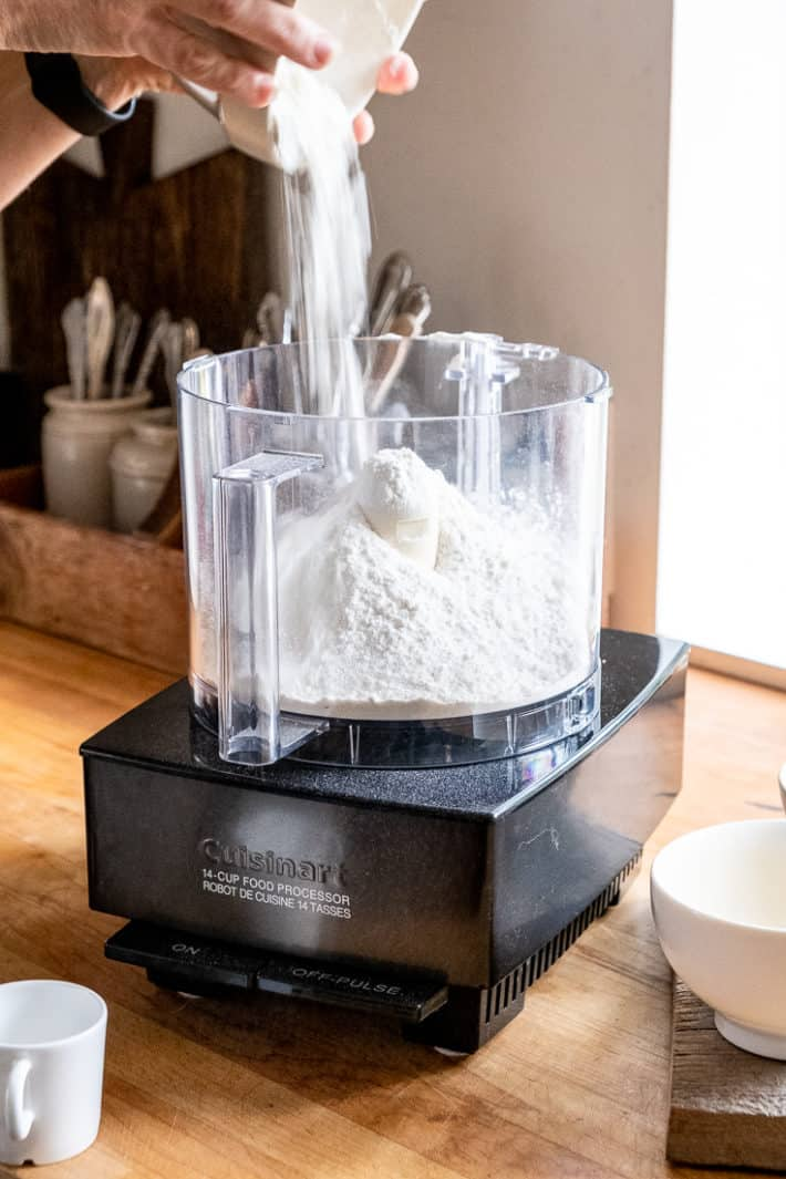 Flour being poured out of an ironstone bowl into a food processor on a butcher block countertop.