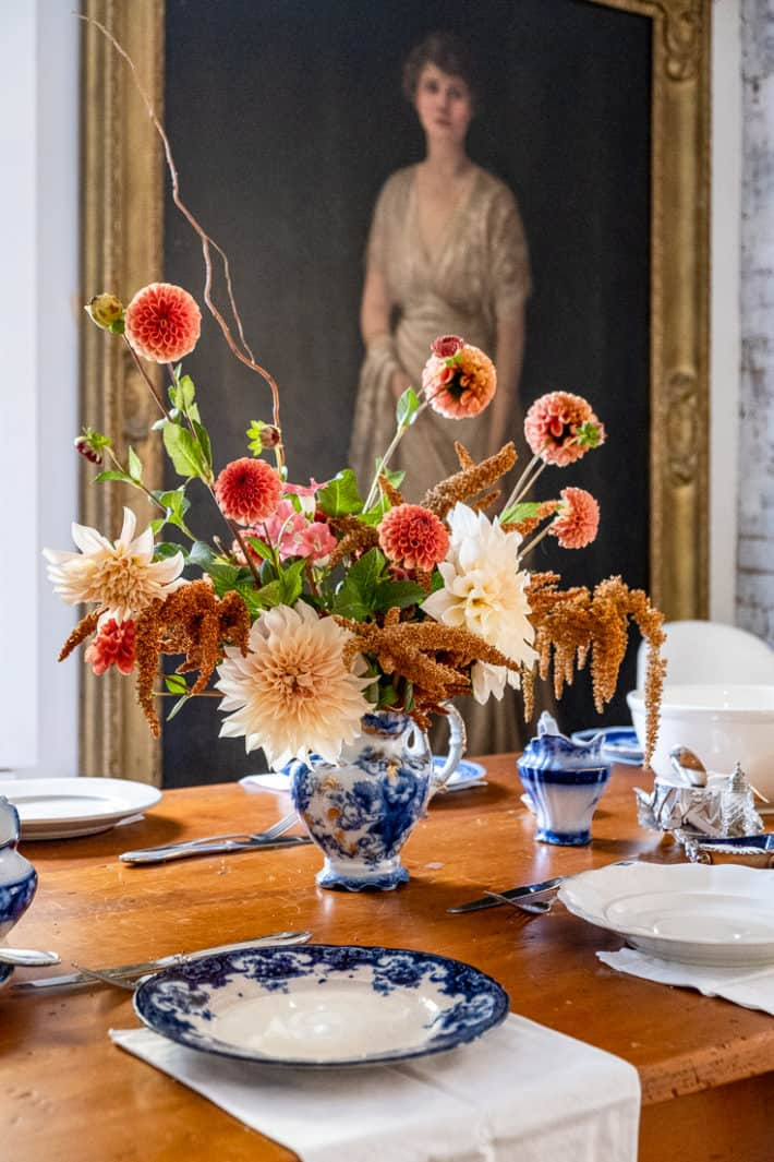 A Thanksgiving centrepiece of ice cube dahlias, hot biscuits amaranth and cornel bronze dahlias sits in a flow blue jug.