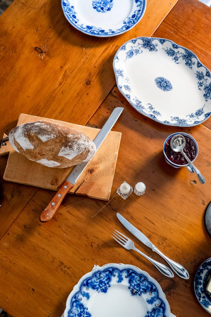 Freshly baked bread sits on a cutting board with a serrated knife on a harvest table with flow blue dishes around.