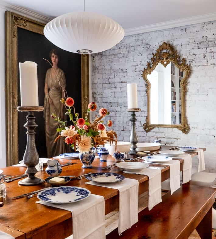 A dining room set for Thanksgiving dinner on a harvest table with a painted white brick wall and full sized antique portrait in the background.