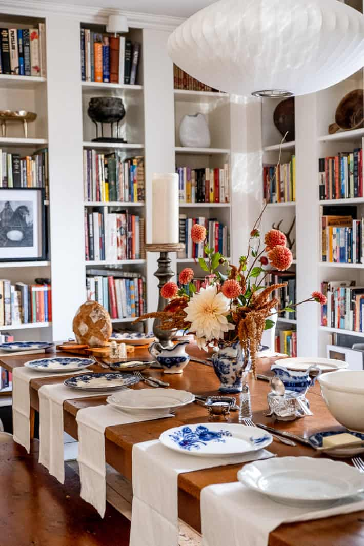 Harvest table in room surrounded by built in bookcases set for Thanksgiving dinner with blue and white plates and rustic dahlia flower arrangement in centre of table.