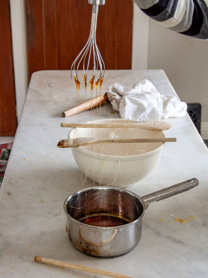 Strands of melted sugar hang down from a whisk to a pot on a marble countertop.