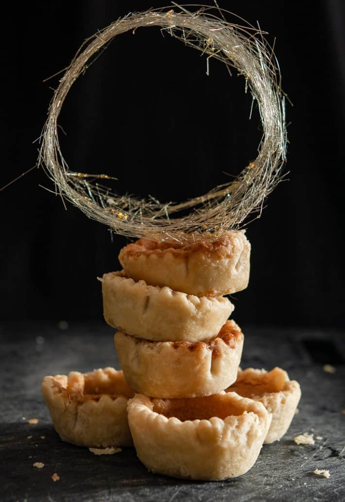 A gold ring of spun sugar sits on top of a stack of butter tart desserts.