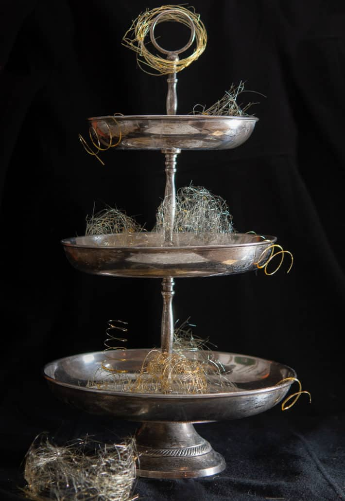 Pieces of gold spun sugar on a vintage 3 tier silver dessert tray with a black background.