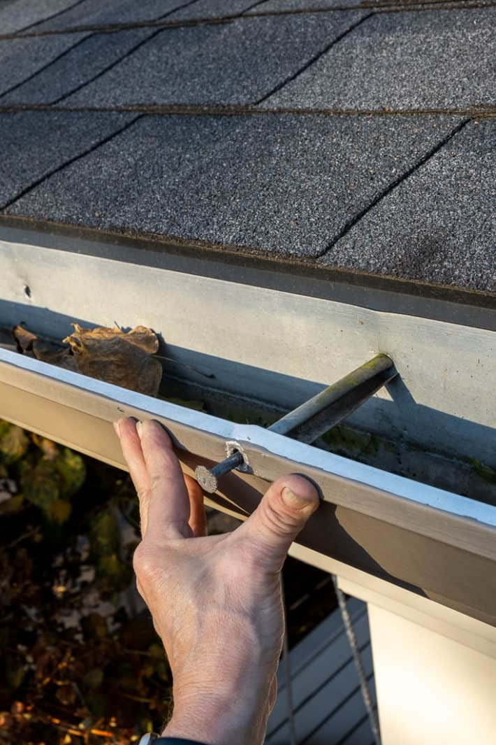 A hand pushing a loose gutter tight against the fascia.