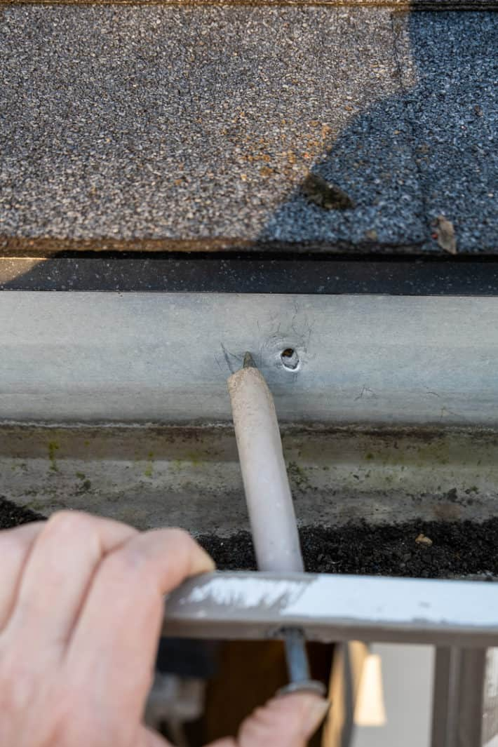 Lining up a gutter spike to the left of its original hole.