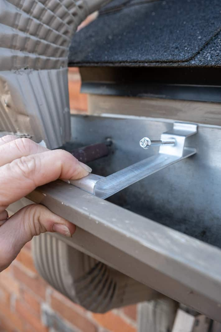 Pushing a gutter bracket under the lip of the eavestrough before screwing it into the home's fascia.