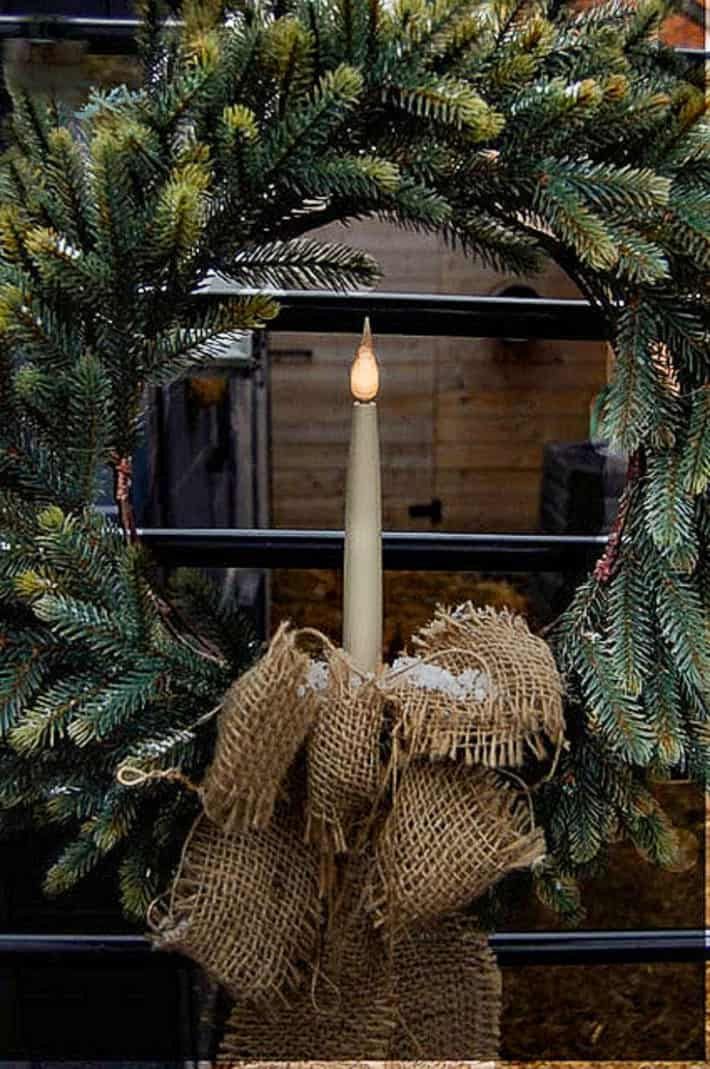 Ikea Christmas wreath with a single battery operated candle in the centre with burlap bow.