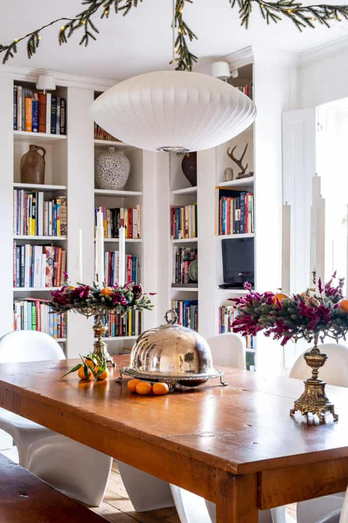 White bookcases surround a wood harvest table decorated with candelabras festooned with dried flowers.