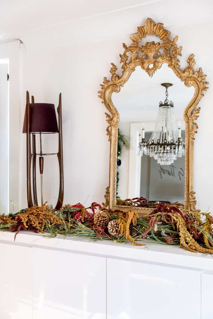 A large ornate gold mirror on a white lacquer buffet with garland holds the reflection of a crystal chandelier.