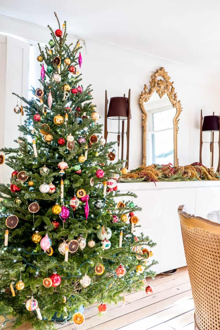 Christmas tree decorated with antique glass ornaments, dried orange slices and DIY flameless Christmas tree candles.