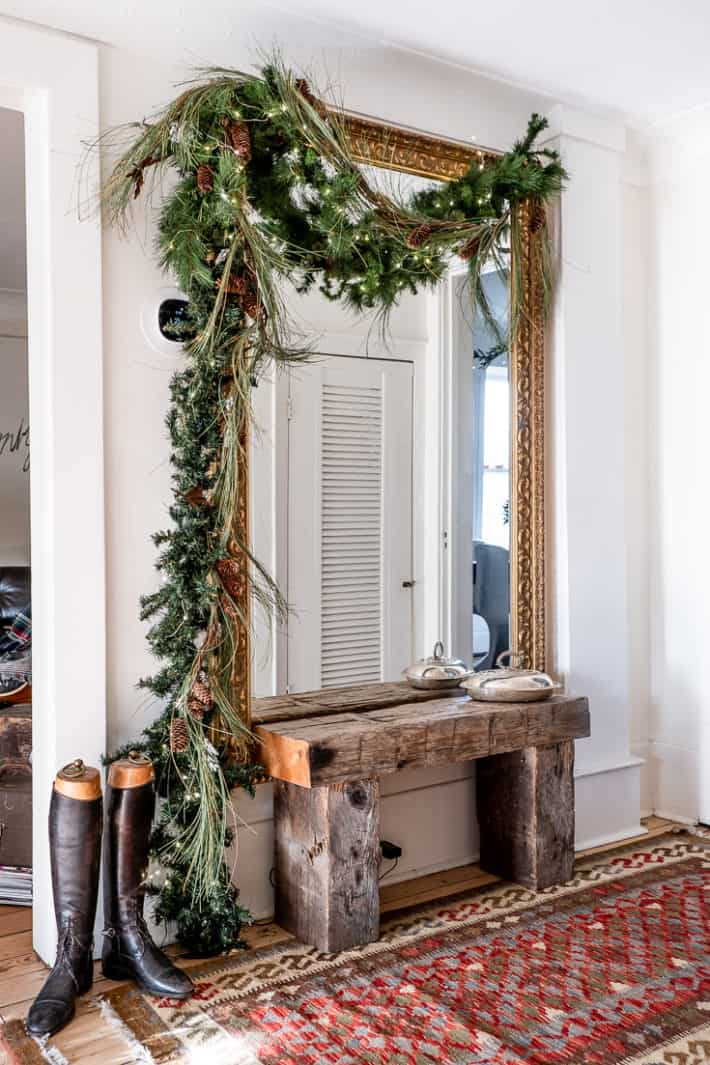 Mixed artificial garland swags over a huge ornate gold mirror on the wall, with riding boots and a bench beneath.