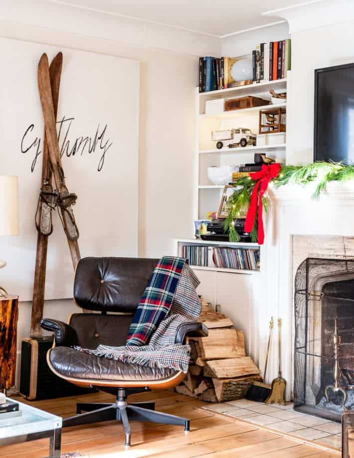 A pair of antique wooden skiis lean against a wall behind an Eames recliner in front of a fireplace.