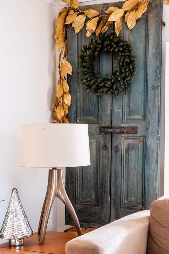 Antique blue painted French shutters with iron hardware decorated with a plain Christmas wreath and gold leaf garland.