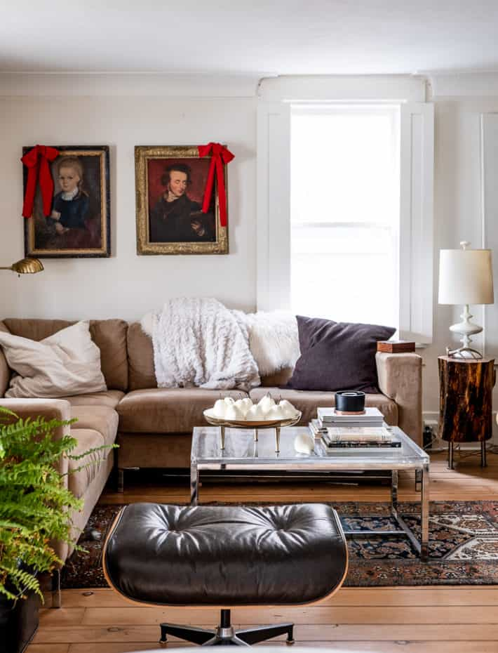 A cozy living room with antique wood floors and dark, portraits on the white walls, accessorized with red velvet fabric bows.