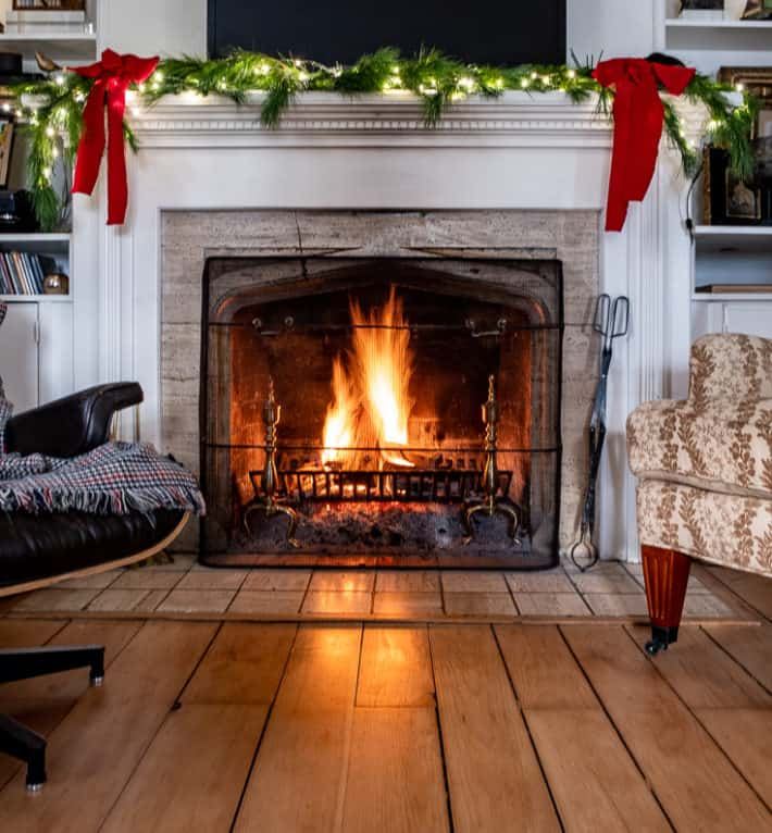 A white mantled fireplace, with a fire roaring in the hearth and evergreen branches with red bows on the mantle.