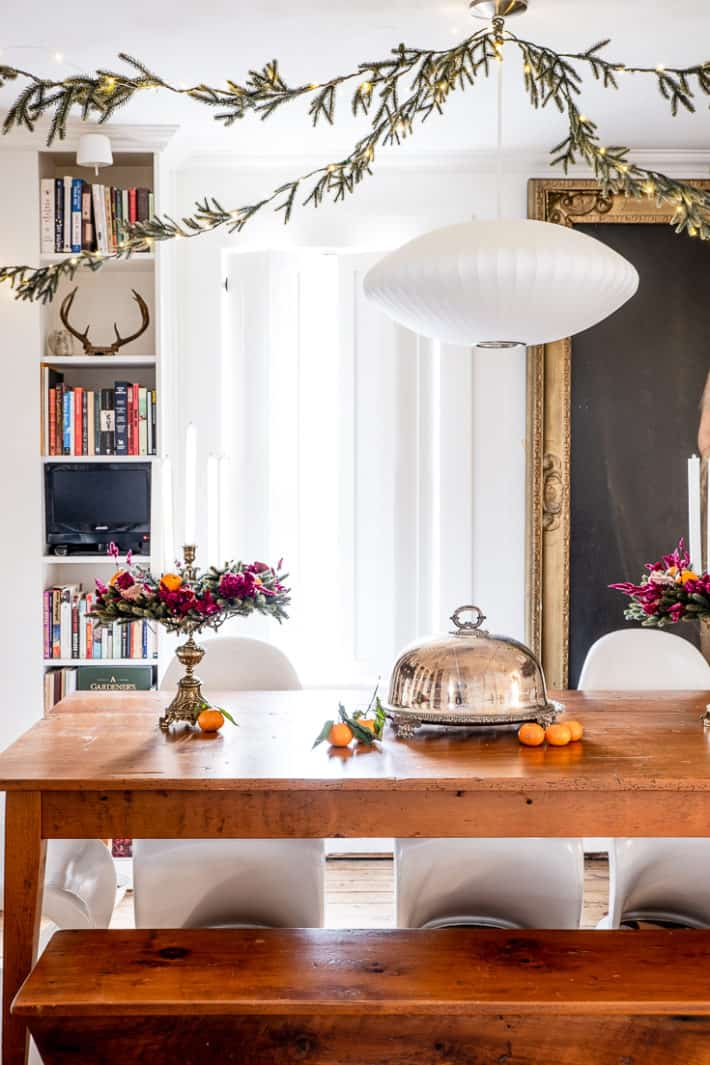 Thin imitation evergreen runs from corner to corner of the ceiling in this dining room for a Victorian Christmas look.