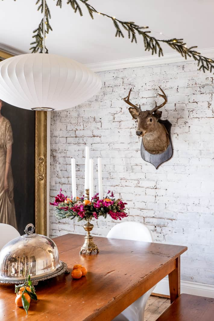 A deers head hangs on a white painted brick wall, with a harvest table and modern chairs before it.