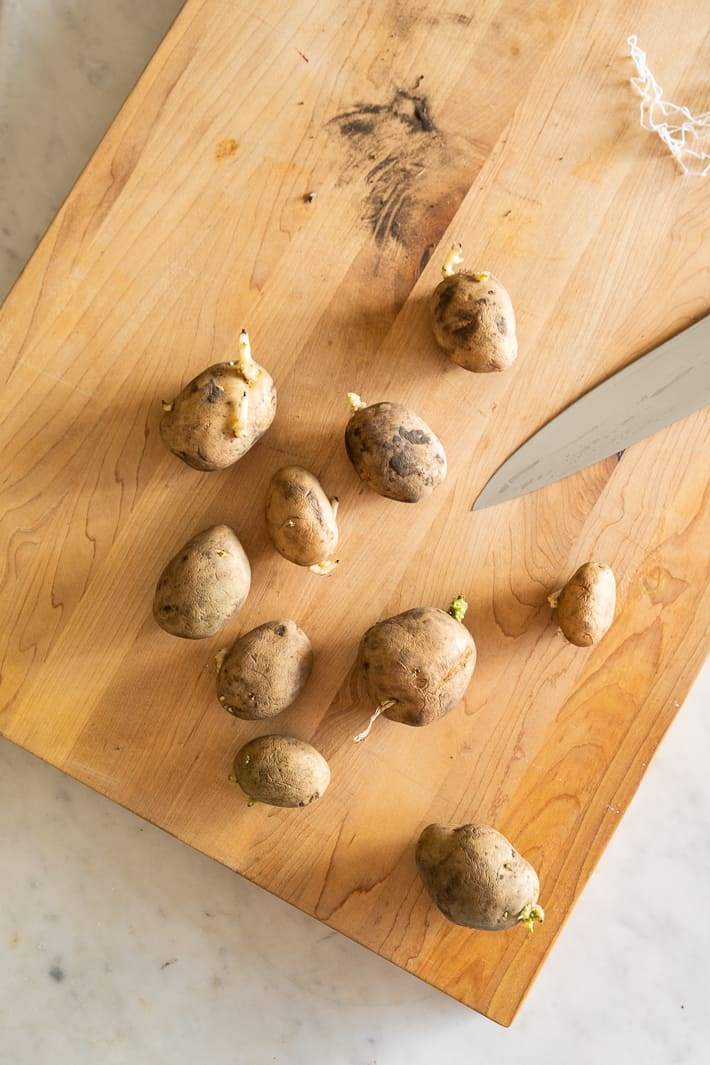 Seed potatoes lay on a cutting board seen from overhead.