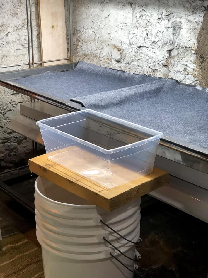 A clear plastic bin sits on a stack of buckets to make sure it's even with the capillary mat edge.