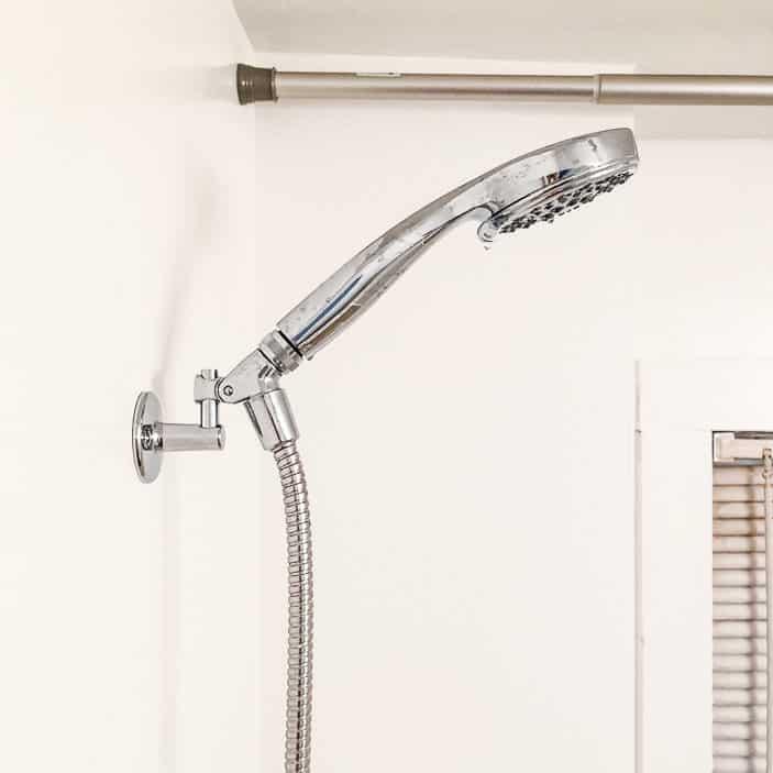 Diverter shower installed in white bathroom.