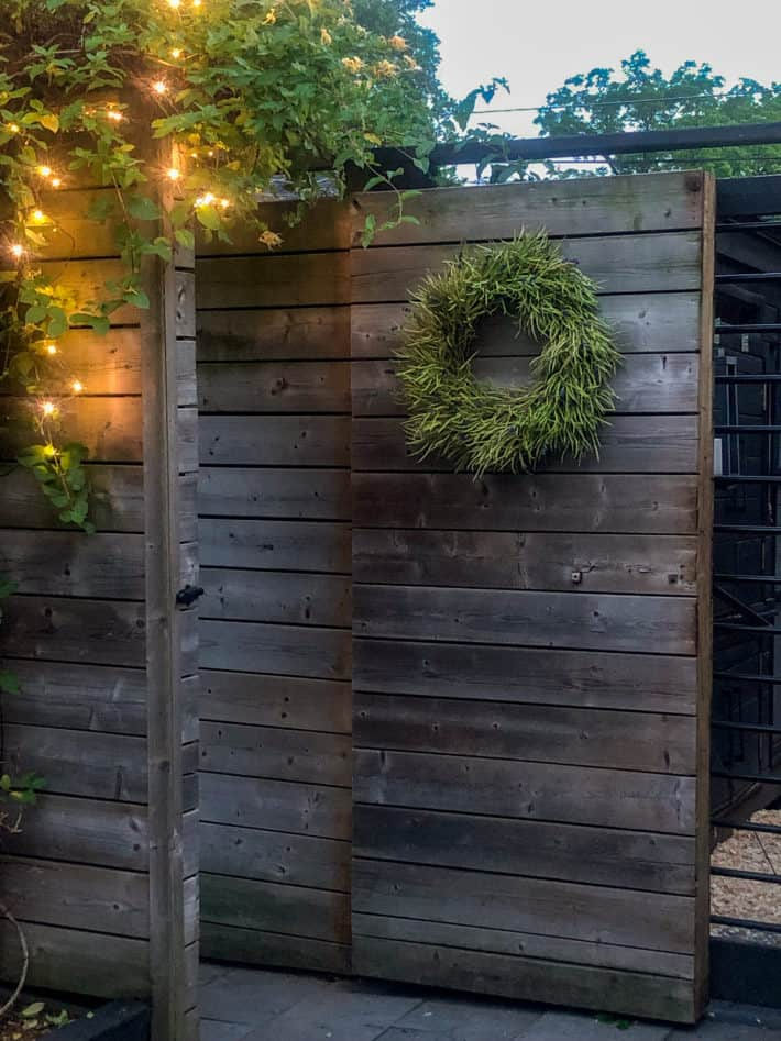 DIY wreath hangs on a modern fence gate with horizontal fencing boards.