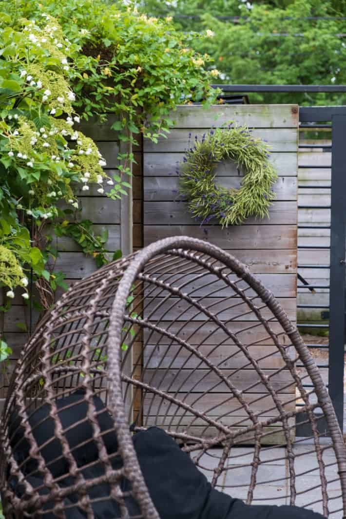 """A modern round wicker chair sits in front of a gate with a 12"""" wreath made of kale seed pods and lavender stems."""