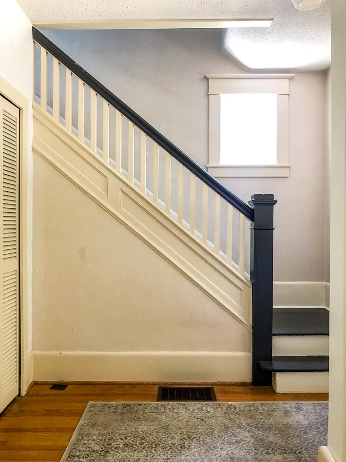 1920's staircase transformation with black bannister, newel post and steps.