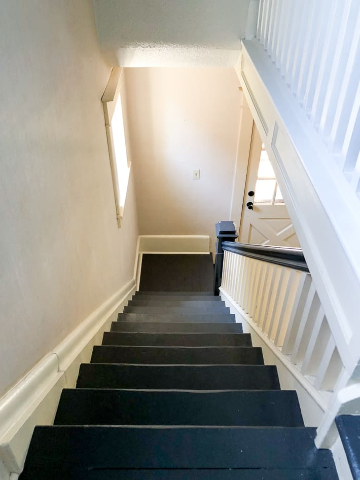 Painted staircase with black, newel post, bannister and white spindles and risers.