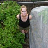 Karen Bertelsen stands in her large community vegetable garden.