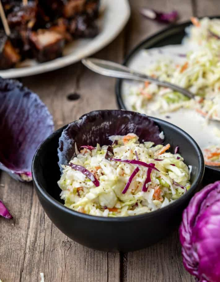 Traditional coleslaw in a small black bowl lined with a red cabbage leaf.